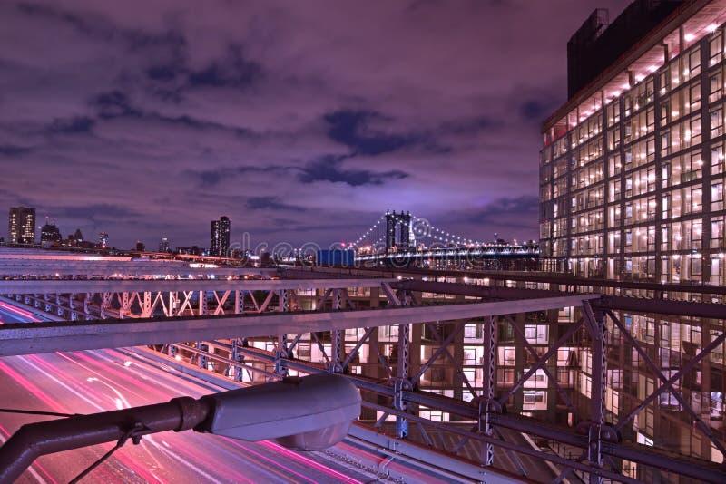Brooklyn bro på skymning med purpurfärgad violett tontajming och en väl tänd byggnad på den högra och tunga trafiken under