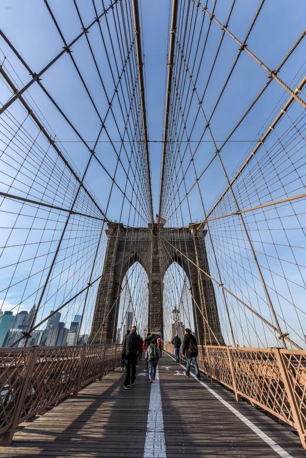 Brooklyn bro på solnedgången med folk som går över i sikt royaltyfri bild