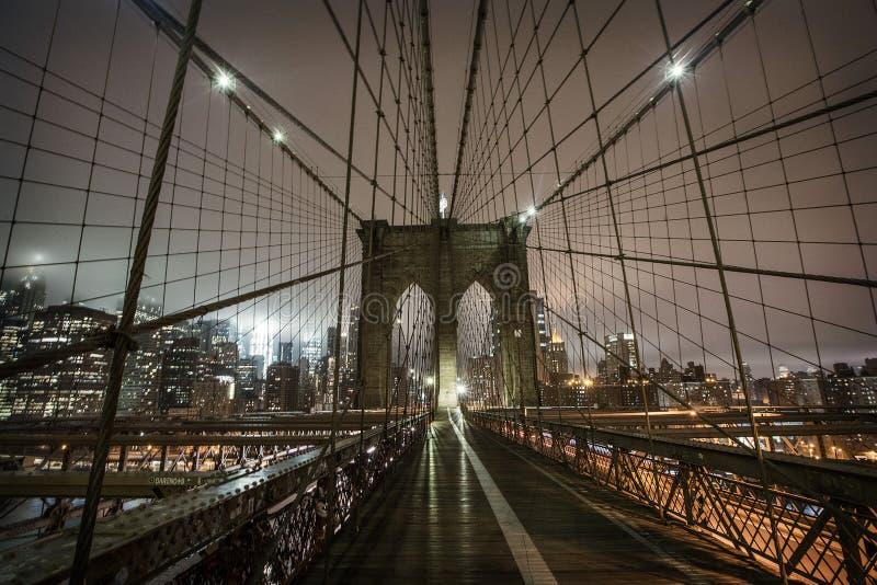 Brooklyn bro under en dimmig natt i New York royaltyfria bilder