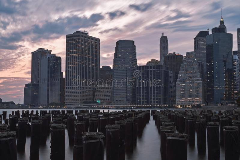 A Brooklyn cola no por do sol com opinião da skyline, citylights New York, EUA foto de stock royalty free