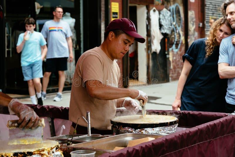 Brooklyn Flea Market in DUMBO in New York. New York City, USA - June 24, 2018: Man preparing fresh food in Brooklyn Flea Market in DUMBO. It includes vendors of stock images