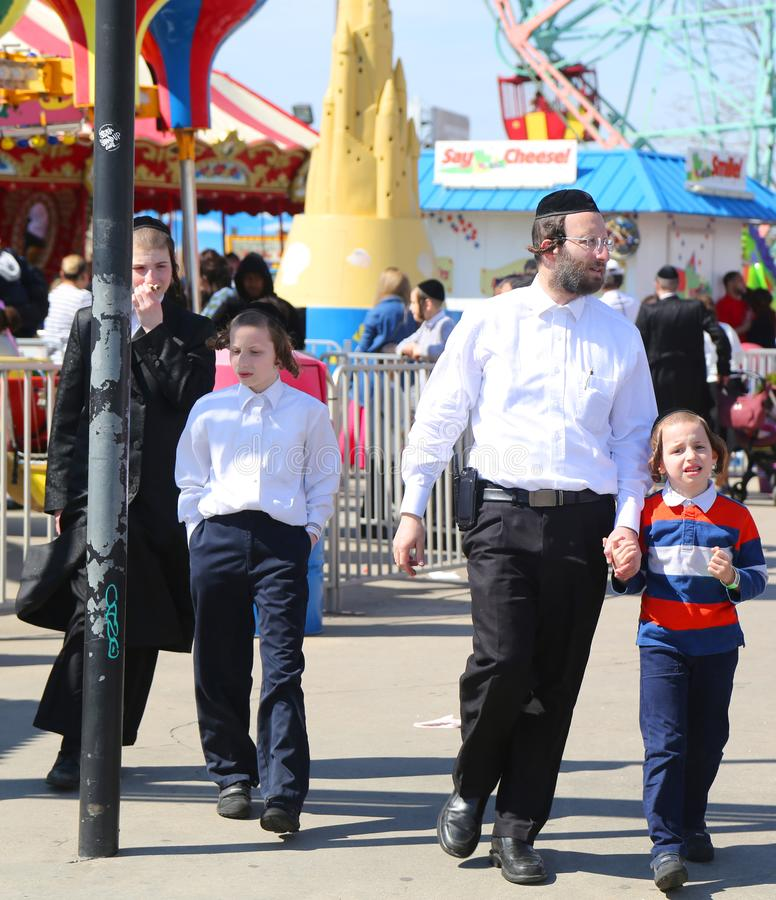 Jewish orthodox family enjoy outdoors during Passover at Coney Island Luna Park in Brooklyn, New York royalty free stock photography