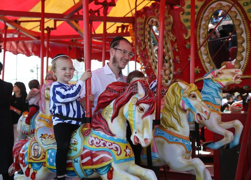 Jewish orthodox family ride Coney Island carousel in Luna Park during Passover at Coney Island Boardwalk in Brooklyn stock image
