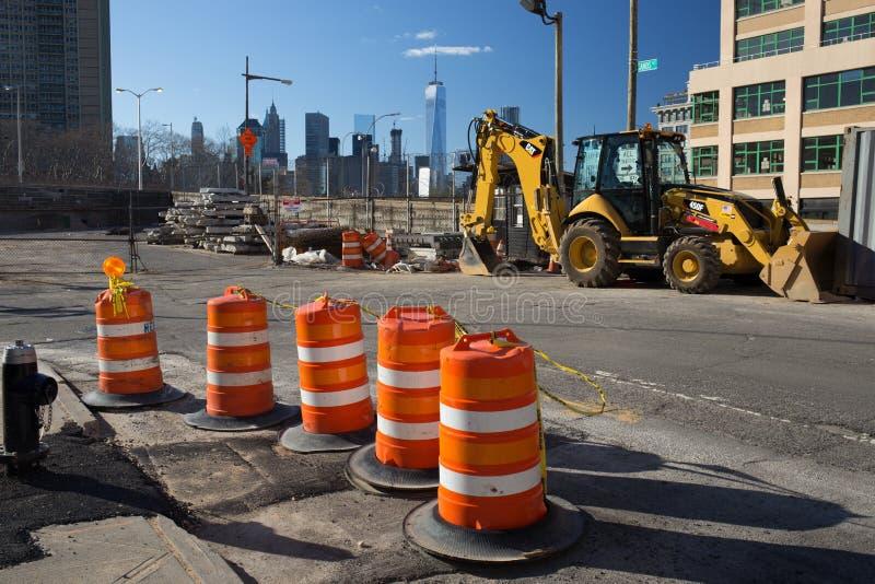 Brooklyn New York - USA - Juli 10 2016: Konstruktionsplats med orange kottar och backhoe med internationell handelmitten och den  royaltyfria bilder