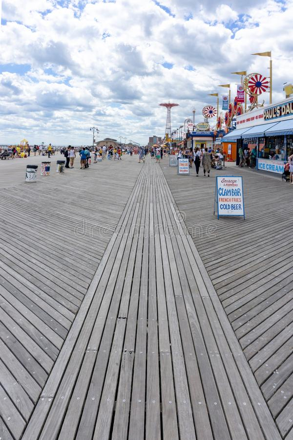 Brooklyn, NY / United States - June 15, 2018: A vertical view of the boardwalk at Coney Island with tourists and admusement park stock image