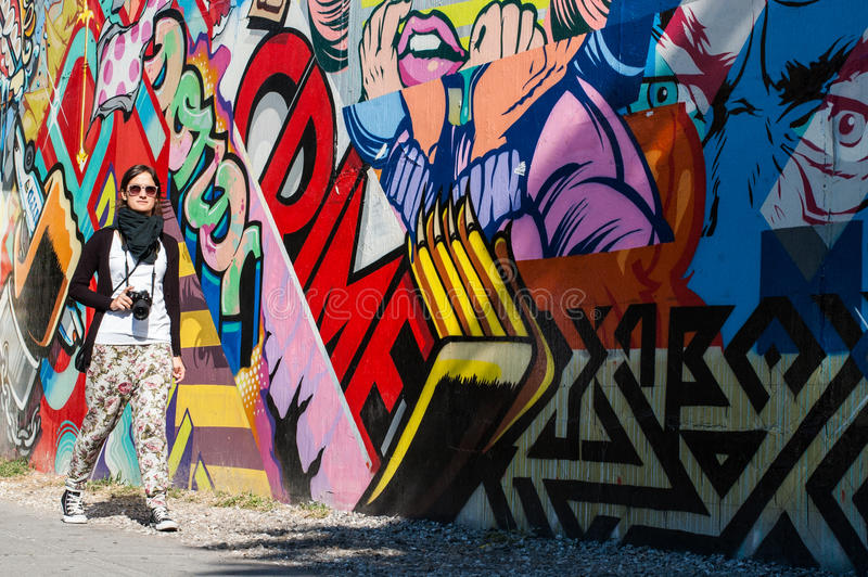 BROOKLYN, NYC, US, October 1 2013: Street art in Brooklyn. Hipster female photographer walking next to a wall of graffiti in royalty free stock images