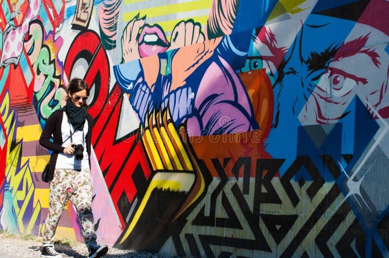 Hipster model walking next to a wall of graffiti royalty free stock image