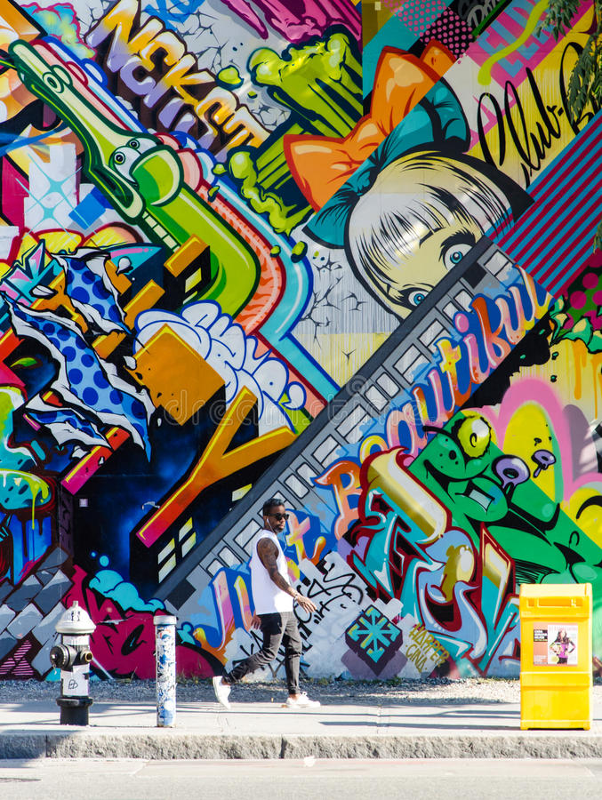 BROOKLYN, NYC, US, October 1 2013: Street art in Brooklyn. Hipster male walking next to a wall of graffiti in Brooklyn, New stock image