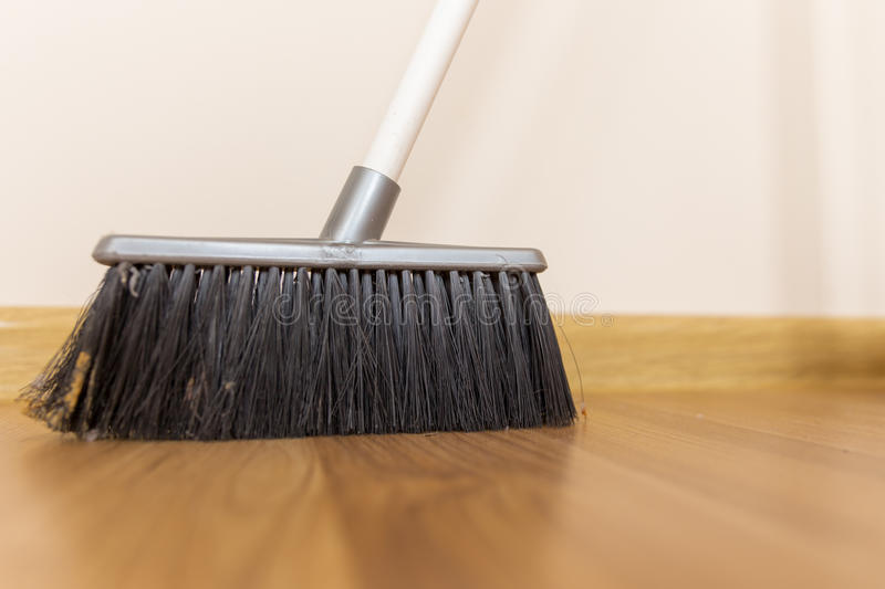 Broom. Sweeping dust with black broom on a wooden floor royalty free stock photo