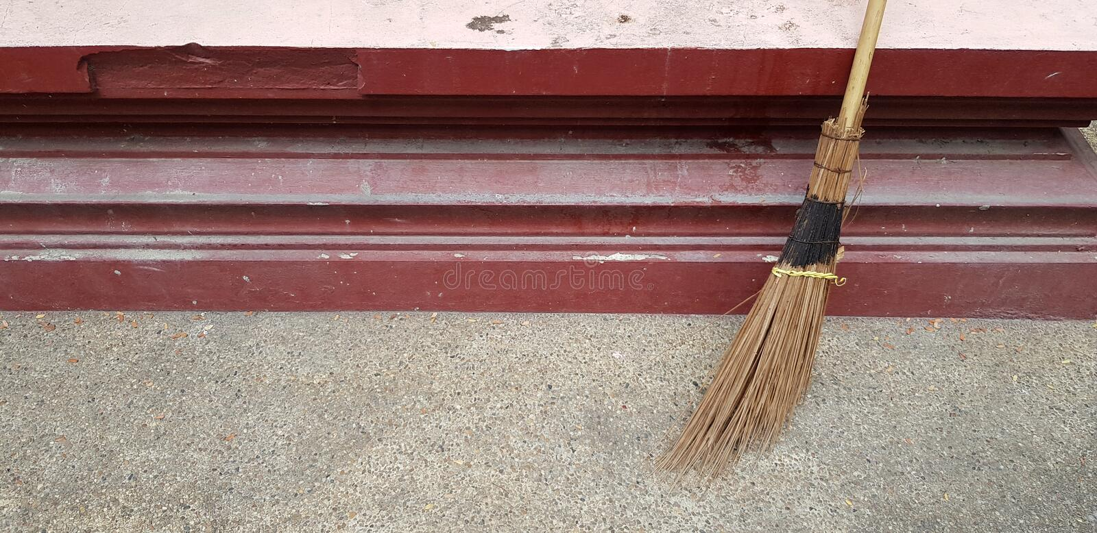 Broom Against the red wall for clean dust and sweep the garbage. With left copy space - Cleaning tool and Housework concept stock photos