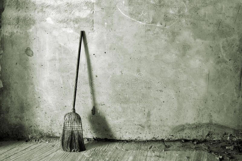 Broom or besom. Old obsolete broom or besom leaning on the gray wall royalty free stock photos