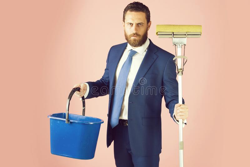 Broom and bucket in hand of bearded man or businessman stock images