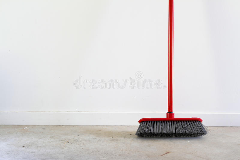 Broom. On floor, blank wall for advertising copy stock photo