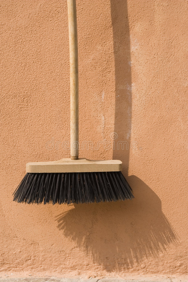 Broom and Shadow. Hanging push broom with shadow royalty free stock photo