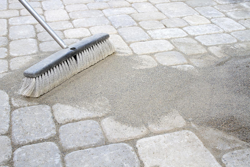 Broom Sweeping Sand into Pavers stock images