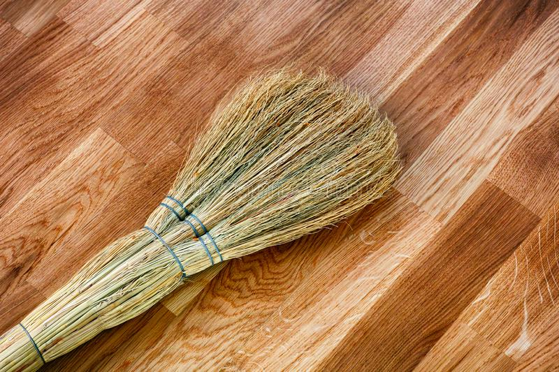 Broom on wooden floor royalty free stock image