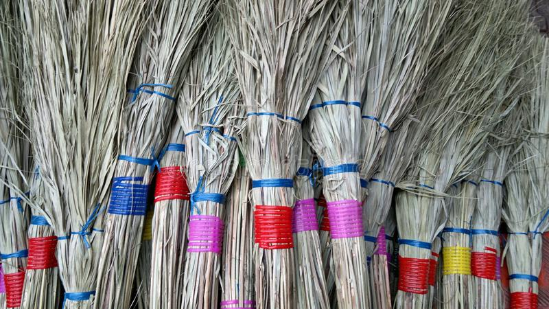 Brooms from plant stalks on a market in India royalty free stock image