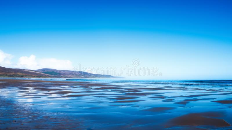 Brora beach with reflections in the wet sand stock photography