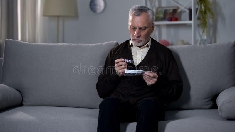 Broschüre des alten Mannes Lesemit Anweisungen für Medikation, riskante Selbstbehandlung stockfotografie