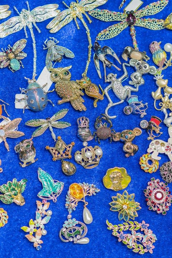 Broschen mit Edelsteinen auf einem blauen Hintergrund Vertikales Foto lizenzfreie stockfotografie