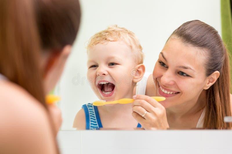 Brossage de dents d'enfant d'enseignement de mère photo stock
