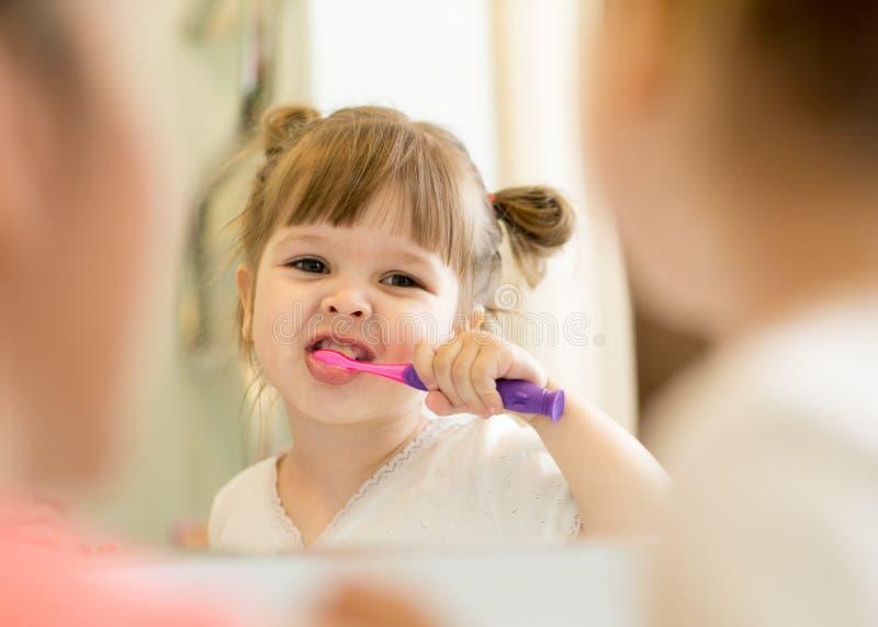 Brossage de dents d'enfant d'enseignement de mère image stock