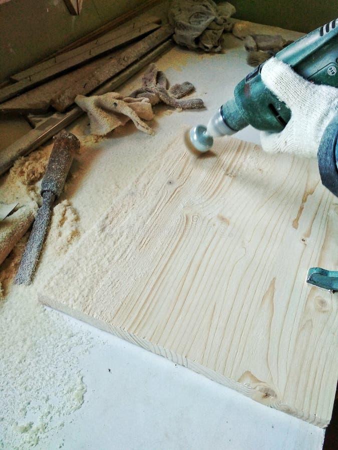 brossage en bois fait main de support de plateau d'objet Le processus de travailler un man& x27 ; main de s dans un gant photographie stock