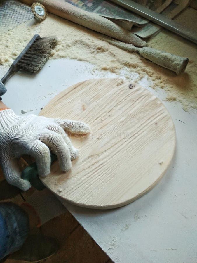 brossage rond de support de plateau d'objet en bois fait main Le processus de travailler un man& x27 ; main de s dans un gant photo stock