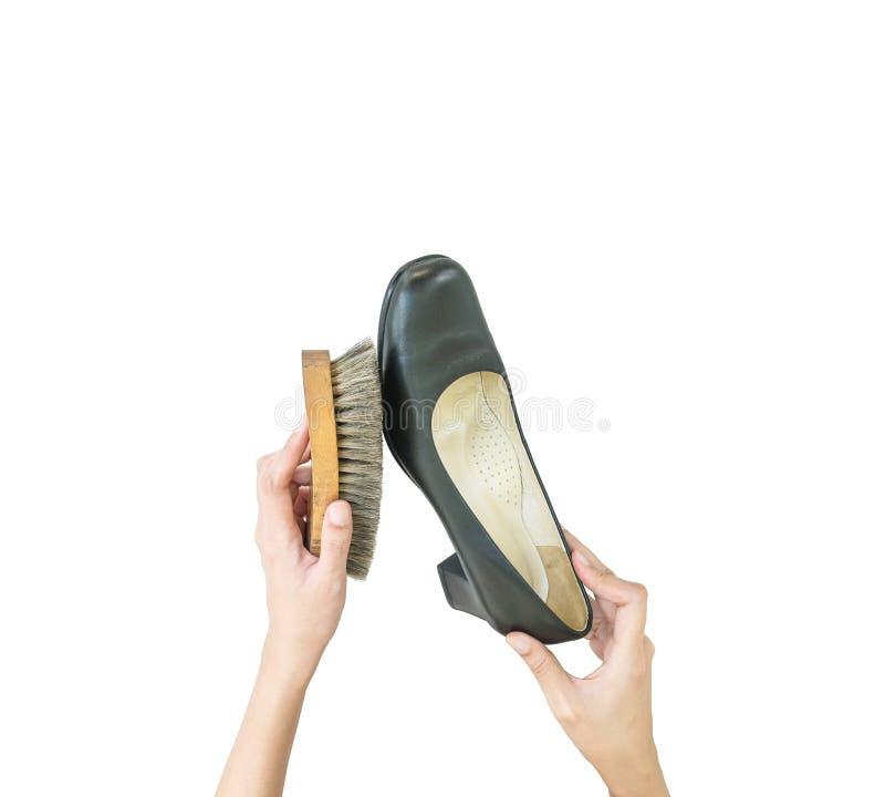 Brosse à chaussures en bois d'utilisation de femme de plan rapproché vieille pour frotter la chaussure noire d'isolement sur le f photos stock