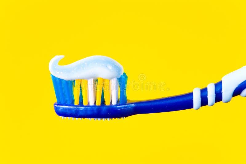 Brosse à dents bleue avec la pâte dentifrice bleue sur un fond jaune images libres de droits
