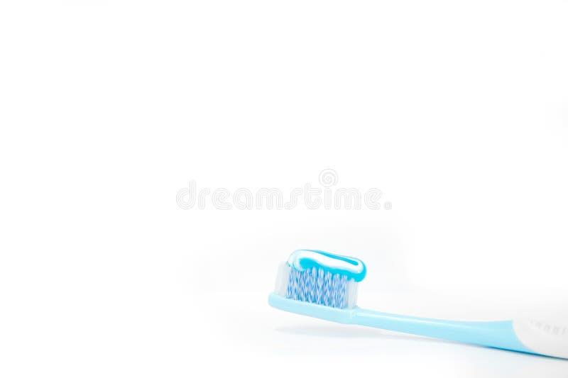 Brosse à dents bleue avec la pâte dentifrice pour le matin régénérant sur le blanc photos libres de droits