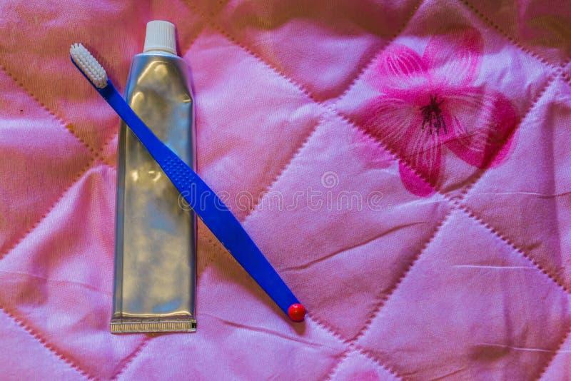 Brosse à dents simple avec un tube vide argenté de pâte dentifrice, d'isolement sur un fond rose photos stock