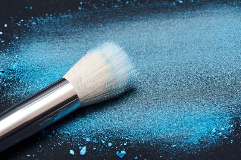 Brosse blanche de maquillage sur la poudre bleue enduite photo libre de droits