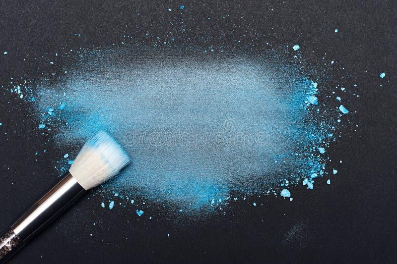 Brosse de beauté et poudre bleue meared de maquillage photographie stock