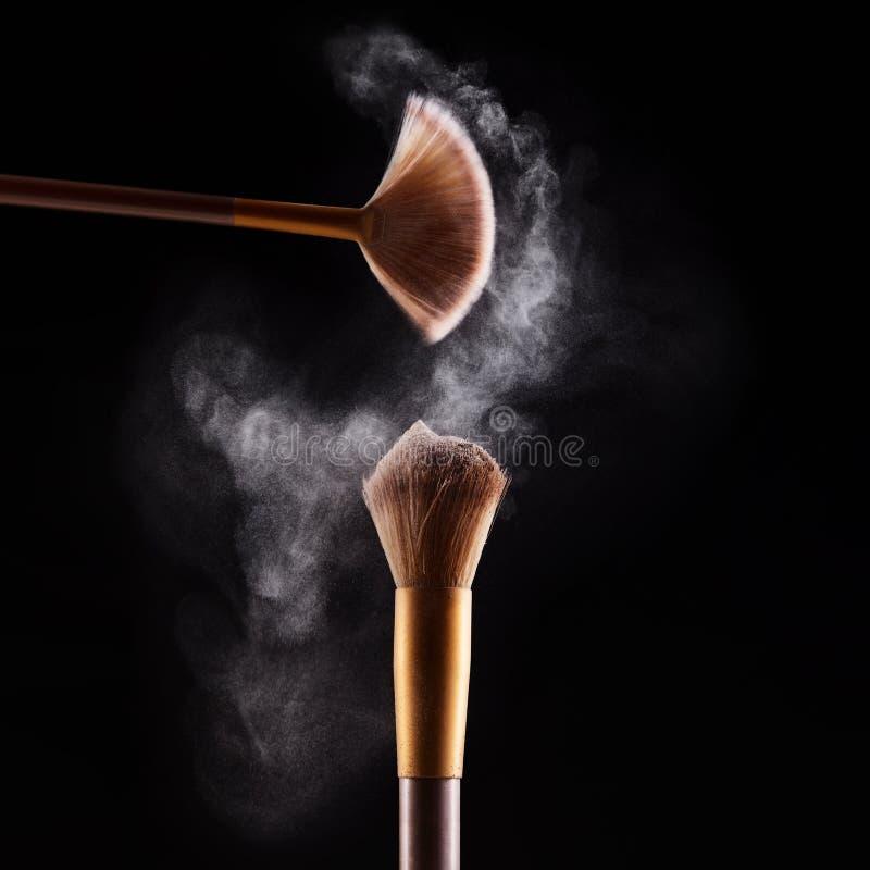 Brosse de maquillage avec l'explosion bleue de poudre images stock