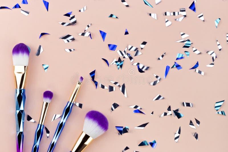 Brosse de maquillage d'ombre de licorne avec des papiers d'étincelle de partie sur p en pastel image libre de droits