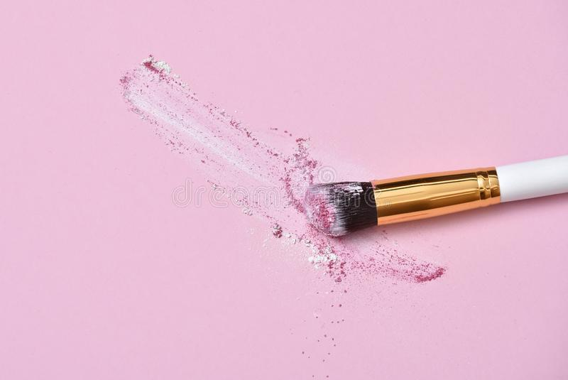 Brosse de maquillage sur le fond rose avec la poudre color?e de colorant Vue sup?rieure photographie stock