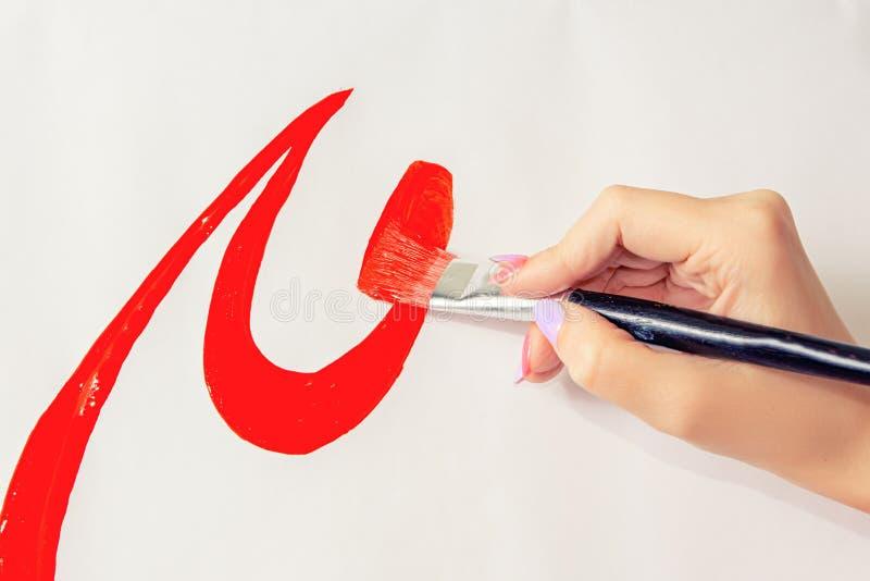 Brosse de plan rapproché dans les mains de l'artiste, peinture d'aquarelle photo stock