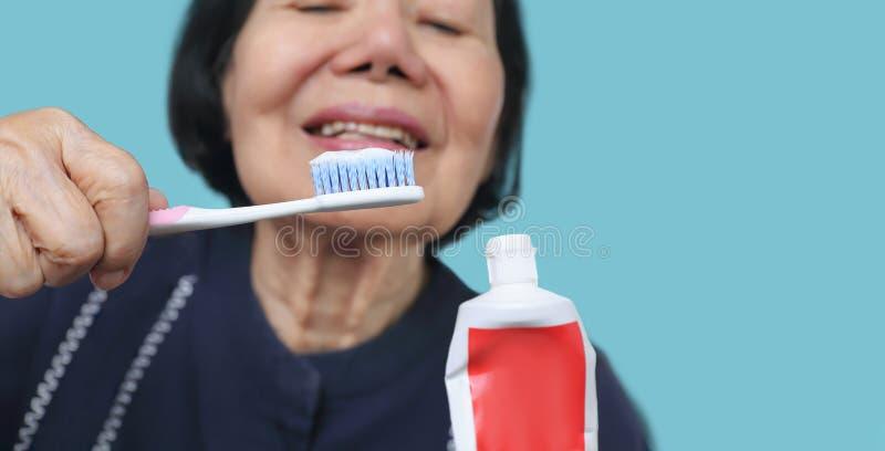 Brosse ? dents de essai d'utilisation de femme ag?e asiatique, tremblement de main Sant? dentaire photographie stock