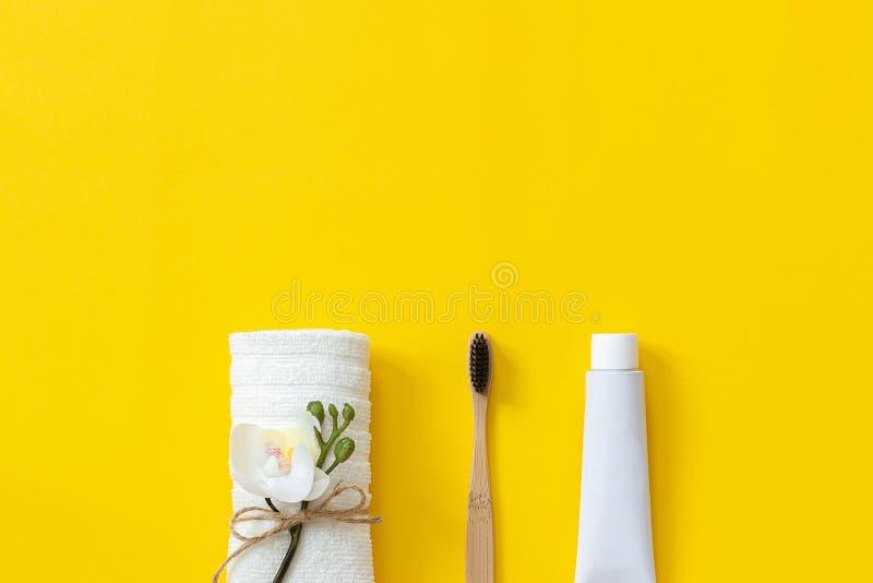 Brosse en bambou qui respecte l'environnement naturelle, serviette blanche et tube de p?te dentifrice R?gl? pour laver sur le fon photos libres de droits