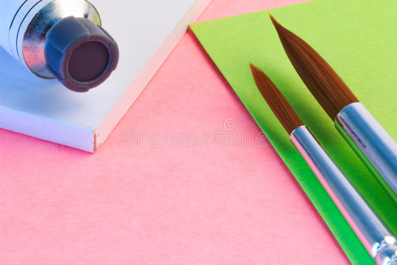 Brosse et tube d'aquarelle sur la note de papier Pinceau et tube de couleur simples de l'eau sur le papier images libres de droits
