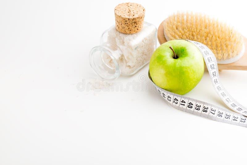 Brosse sèche de massage avec le ruban métrique bouteille de pomme et en verre verte simple avec du sel de mer sur le bureau blanc image stock