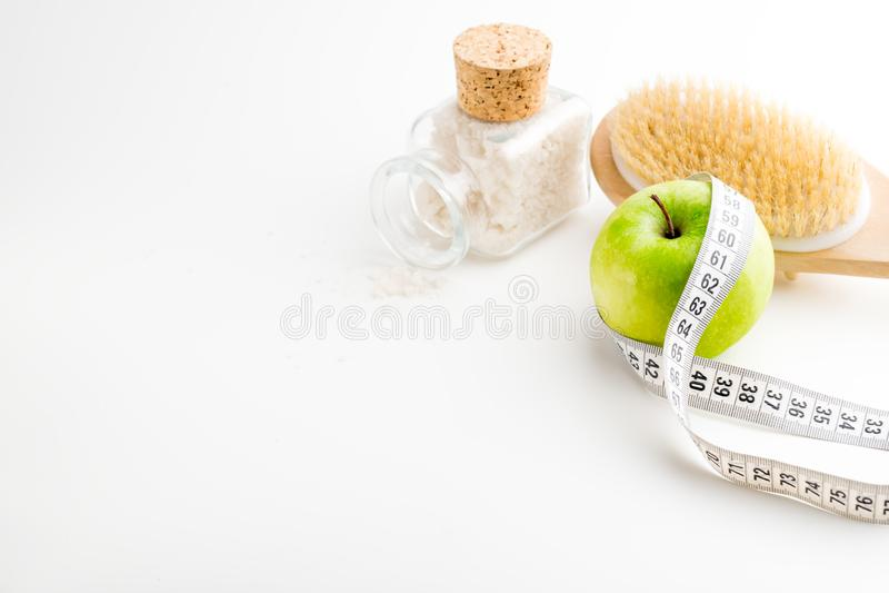 Brosse sèche de massage avec le ruban métrique bouteille de pomme et en verre verte simple avec du sel de mer sur le bureau blanc image libre de droits