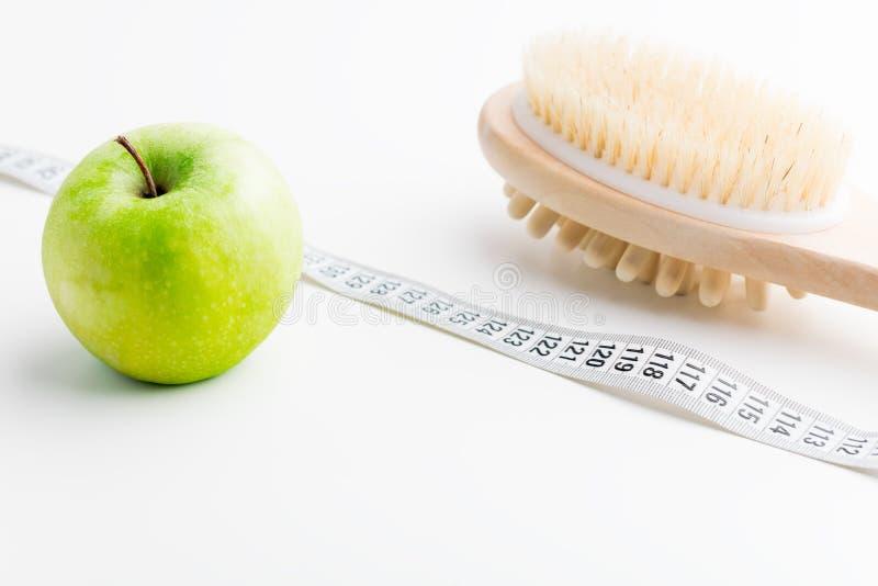 Brosse sèche de massage avec le ruban métrique et pomme verte simple sur le bureau blanc Santé et régime images stock