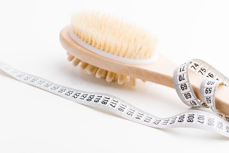 Brosse sèche de massage avec le ruban métrique sur le bureau blanc Santé et régime images libres de droits