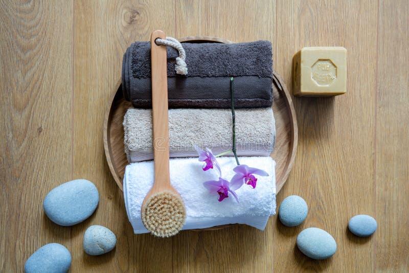 Brosse, serviettes, orchidées et savon qui respecte l'environnement au-dessus des pierres de zen photographie stock