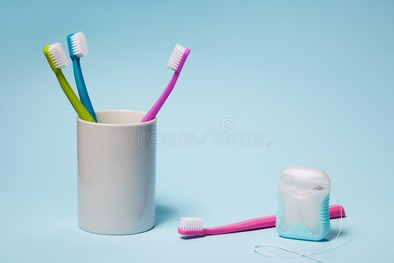 Brosses à dents colorées en tasse et fil dentaire photo stock