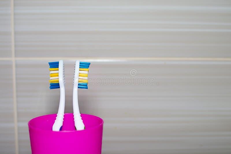 Brosses à dents dans un plan rapproché en verre en plastique Copiez l'espace images stock