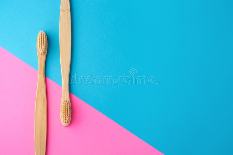 Brosses à dents en bambou sur le rose et le fond bleu image stock