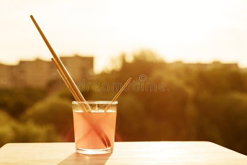 Brosses de l'artiste en verre avec de l'eau sur le rebord blanc en bois de fenêtre Ciel de fond, silhouette de la ville, coucher  photographie stock